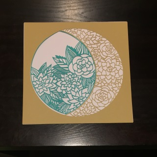 Detailed paper cut with mustard and a turquoise inset.