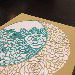 Close up view of the mustard and turquoise succulent papercut.